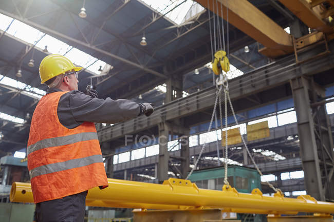 Male worker guiding hydraulic crane in factory — Stock Photo