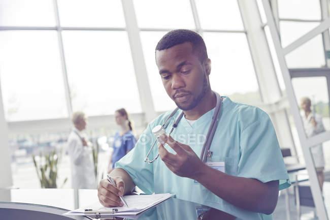 Enfermero con portapapeles comprobación de botella de la medicina en el vestíbulo del hospital - foto de stock