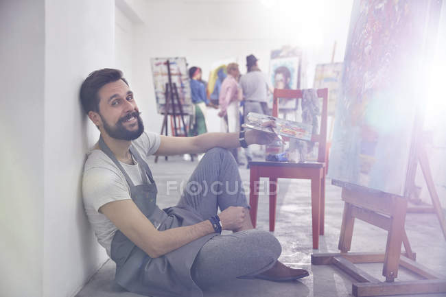 Portrait smiling male artist with palette painting at easel in art class studio — Stock Photo