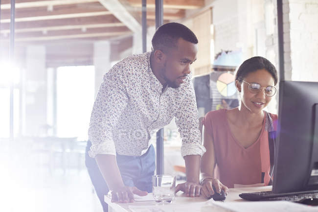 Businessman and businesswoman working at computer in office — Stock Photo