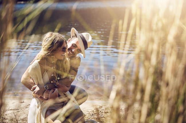 Ласкава молода пара обіймати в сонячному березі річки літо — стокове фото