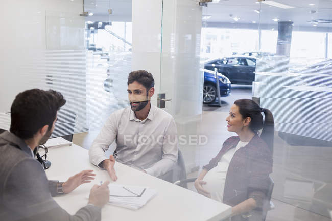 Pregnant couple talking to car salesman, discussing financial paperwork in car dealership office — Stock Photo