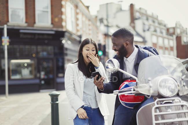Jeune couple riant, en utilisant le téléphone cellulaire au scooter moteur sur la rue urbaine ensoleillée — Photo de stock