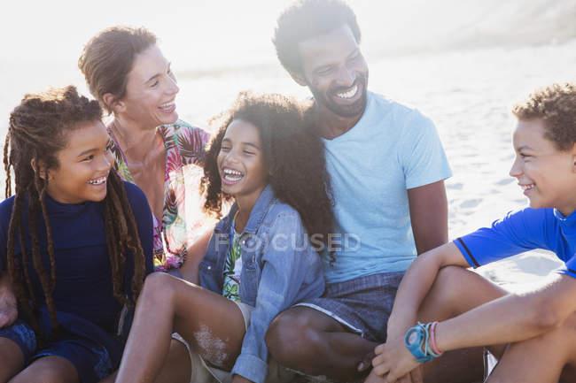 Многонациональная семья смеется на солнечном летнем пляже — стоковое фото