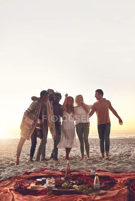 Молодые друзья наслаждаются пикником на солнечном пляже — стоковое фото