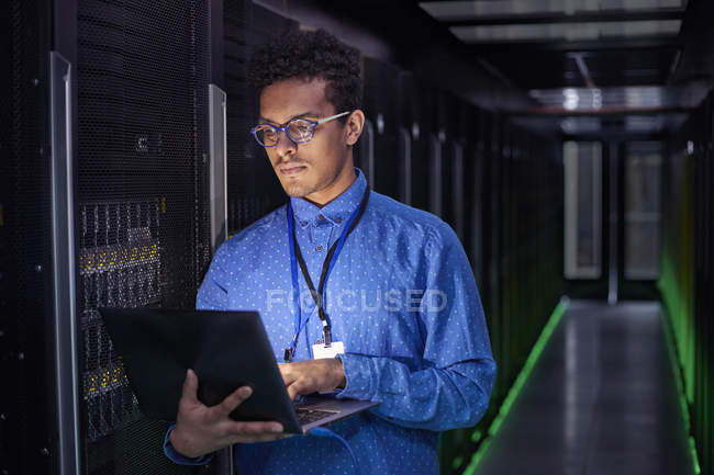 Focused male IT technician using laptop in dark server room — Stock Photo
