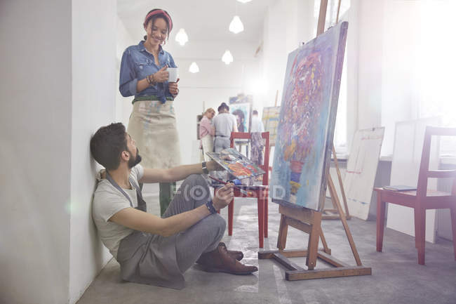Artists drinking coffee painting at easel in art class studio — Stock Photo