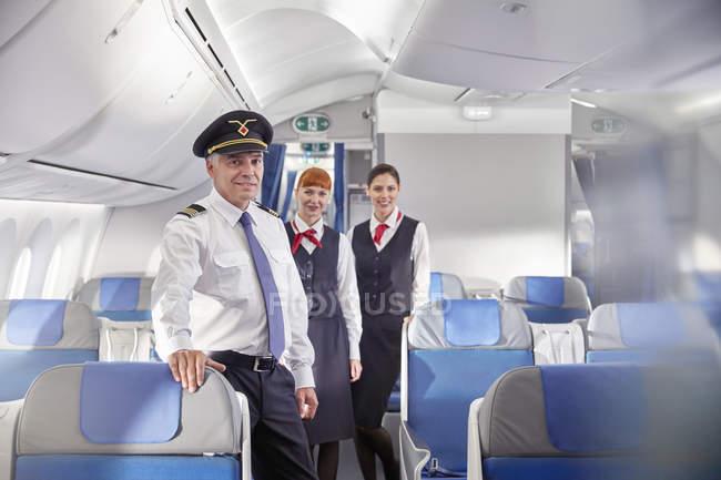 Retrato seguro de piloto y asistentes de vuelo en avión - foto de stock