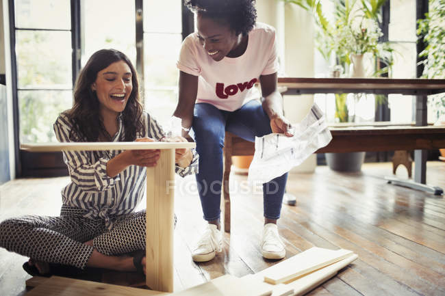 Women with instructions assembling furniture — Stock Photo