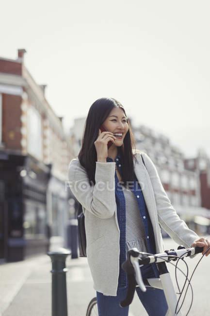 Jeune femme souriante qui fait la navette à vélo, qui parle sur un téléphone portable dans une rue urbaine ensoleillée — Photo de stock