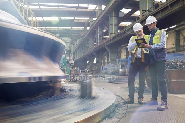 Чоловічий Форман і інженер з цифровий планшетний говорити заводі — стокове фото