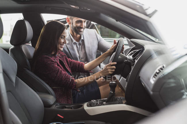 Car salesman and female customer in driver?s seat of new car in car dealership showroom — Stock Photo