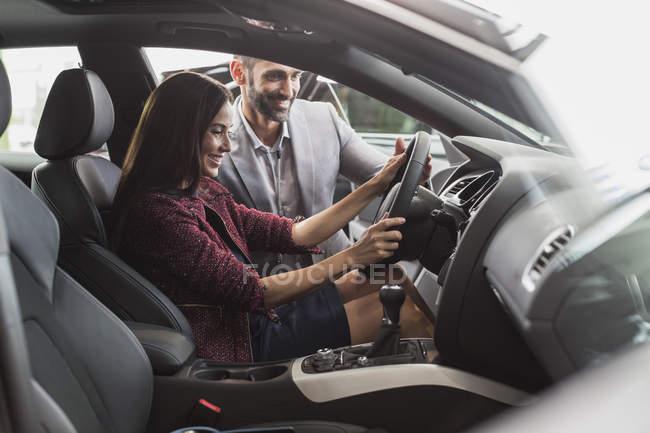 Venditore di auto e cliente femminile nella sede del conducente della nuova auto in concessionaria auto showroom — Foto stock