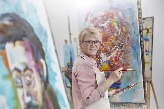 Portrait smiling female artist painting at canvas in art class studio — Stock Photo