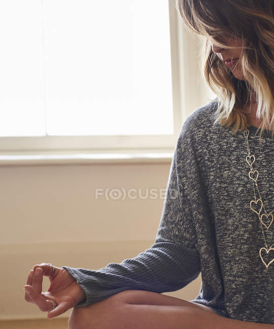 Serene woman meditating in lotus position with hand in gyan mudra — Stock Photo