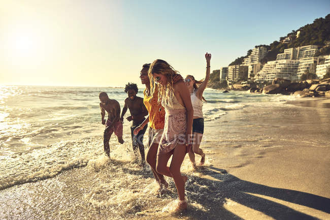 Игривые юные друзья, гуляющие по солнечному летнему океанскому серфингу — стоковое фото