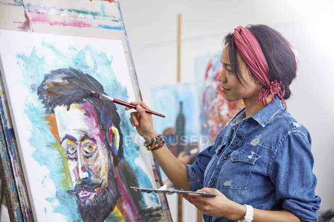 Female artist painting in art studio — Stock Photo