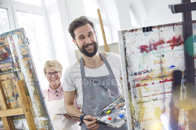 Portrait smiling artists painting at easels in art class studio — Stock Photo