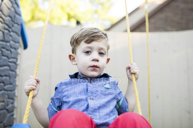 Portrait serious preschool boy swinging on swing — Stock Photo