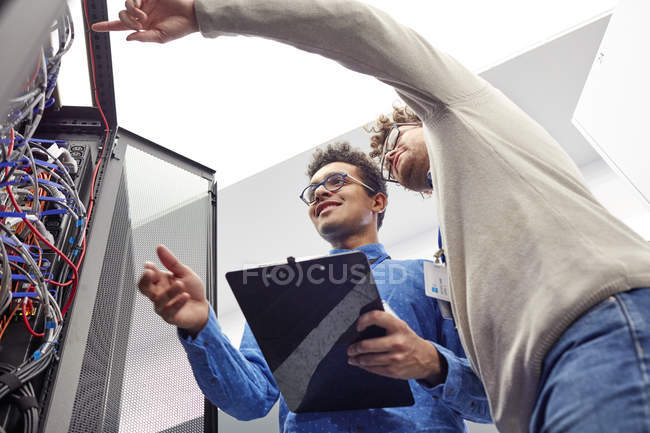 Male IT technicians with clipboard talking at panel in server room — Stock Photo