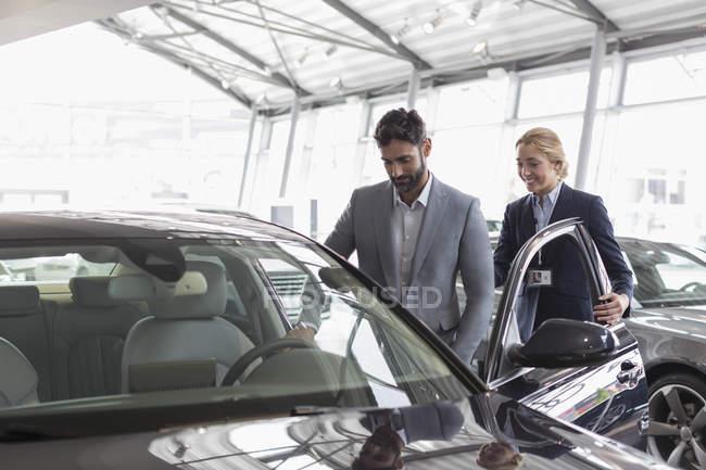 Продавец автомобилей показывает новый автомобиль покупателю-мужчине в автосалоне — стоковое фото