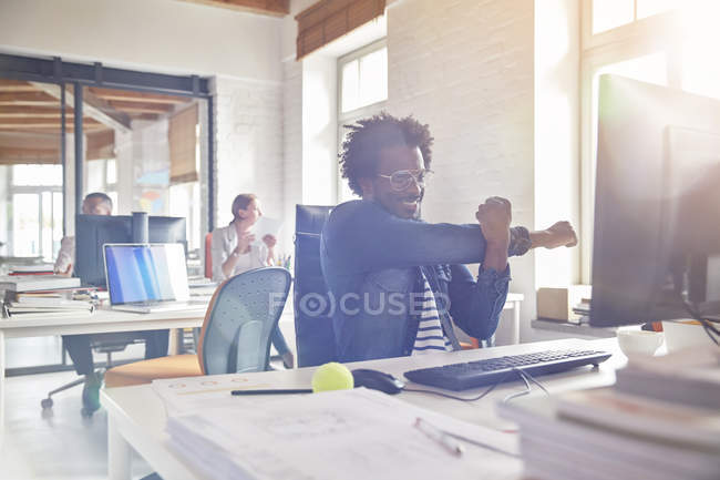 Smiling male design professional stretching arm at computer in office — Stock Photo