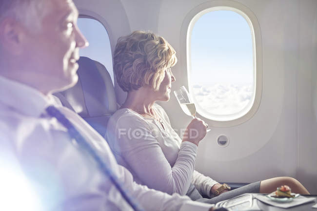 Woman drinking champagne in first class, looking out airplane window — Stock Photo