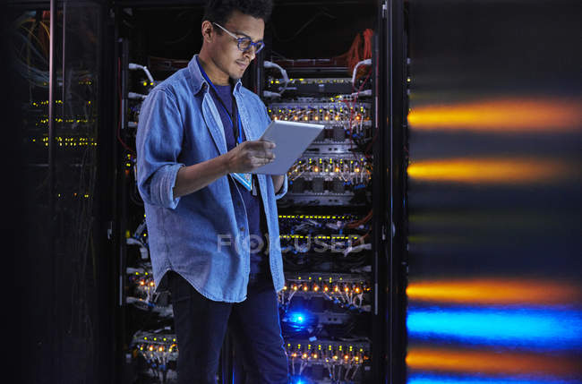 Focused male IT technician using digital tablet at panel in dark server room — Stock Photo