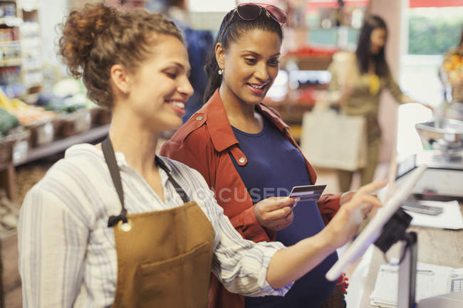 Female cashier helping pregnant woman paying with credit card at grocery store cash register — Stock Photo