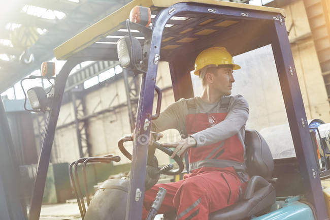 Male worker driving forklift, backing up in factory — Stock Photo