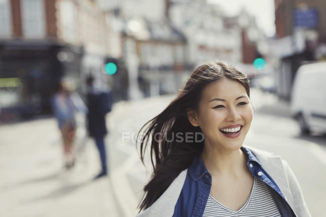 Sorrindo, jovem mulher entusiasmada andando na ensolarada rua urbana — Fotografia de Stock