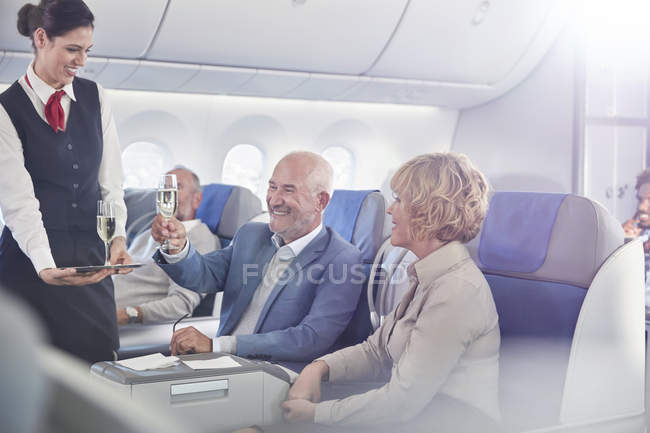Flight attendant serving champagne to mature couple in first class on airplane — Foto stock