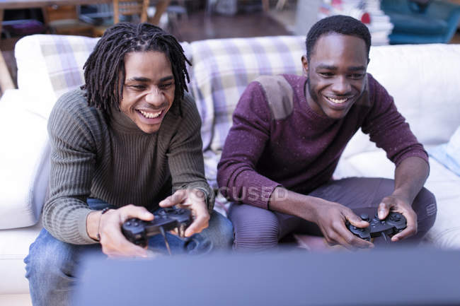 Smiling brothers playing video game on sofa — Stock Photo