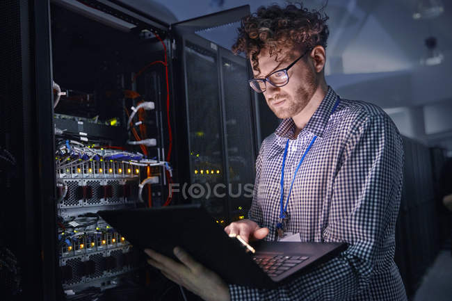 Focused male IT technician working at laptop in dark server room — Stock Photo