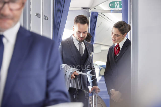 Auxiliar de vuelo ayudando a empresario con pase de abordar en avión - foto de stock
