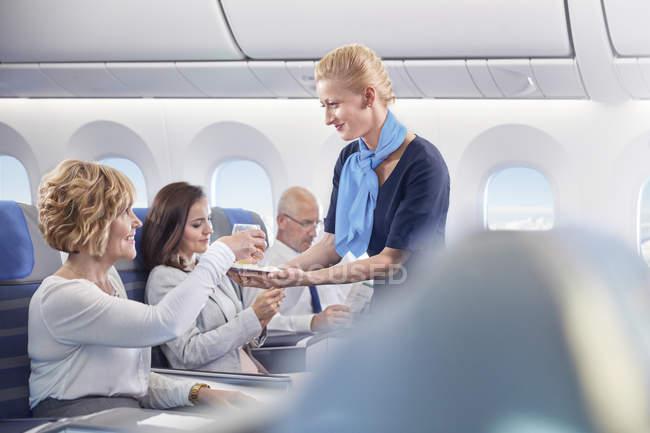 Auxiliar de vuelo servir bebida a mujer en avión - foto de stock