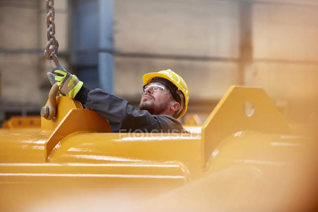 Male worker attaching chain to equipment in factory — Stock Photo