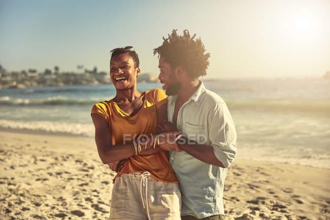 Playful young couple hugging and laughing on sunny summer ocean beach — Stock Photo