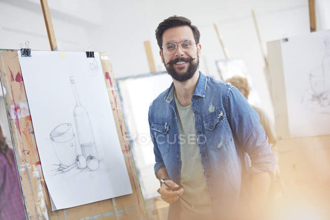 Portrait smiling male artist with beard sketching in art class studio — Stock Photo