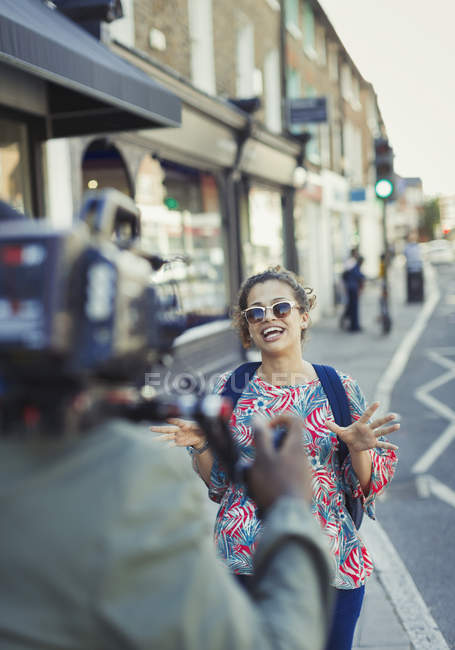 Enthusiastic young woman posing for video camera on urban street — Stock Photo