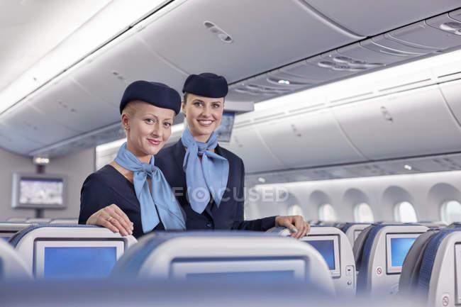 Retrato sorrindo, assistentes de bordo femininas confiantes no avião — Fotografia de Stock
