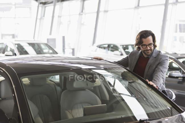 Maschio cliente guardando nuova auto in concessionaria auto showroom — Foto stock