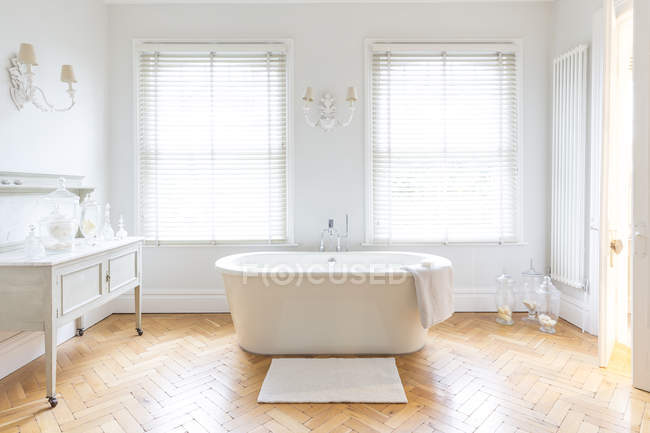 White, luxury home showcase bathroom with soaking tub and parquet hardwood floor — Stock Photo