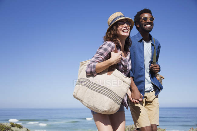 Smiling, affectionate couple holding hands on sunny summer ocean beach — стокове фото