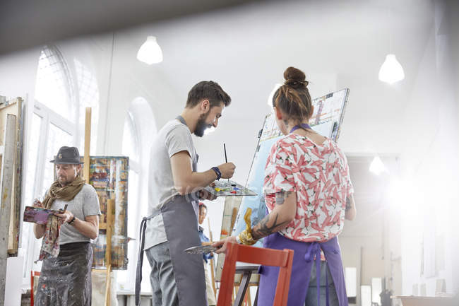 Artists painting at easel in art studio — Stock Photo