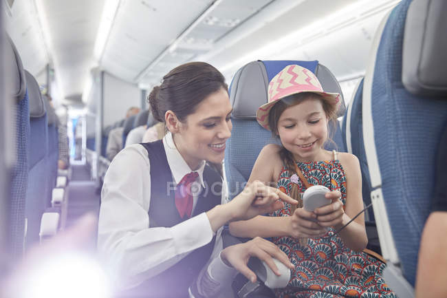 Auxiliar de vuelo ayuda a pasajeros de niña con control remoto en avión - foto de stock