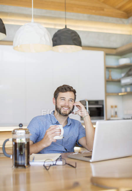 Smiling man drinking coffee and talking on cell phone at laptop — Stock Photo