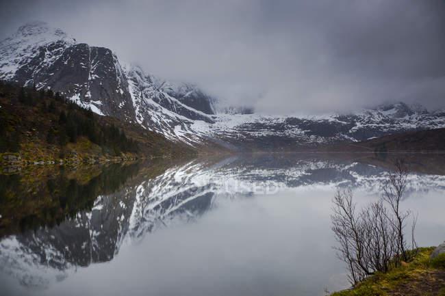 Отражение снежных, извилистых гор в воде, Сторватнет, Лоффель, Норвегия — стоковое фото