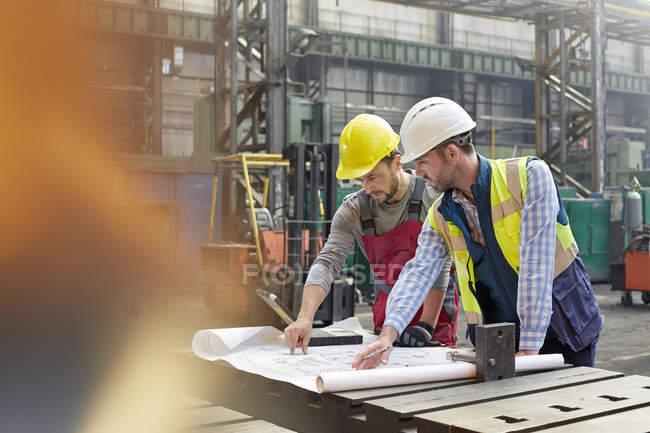 Инженеры-мужчины рассматривают чертежи на заводе — стоковое фото