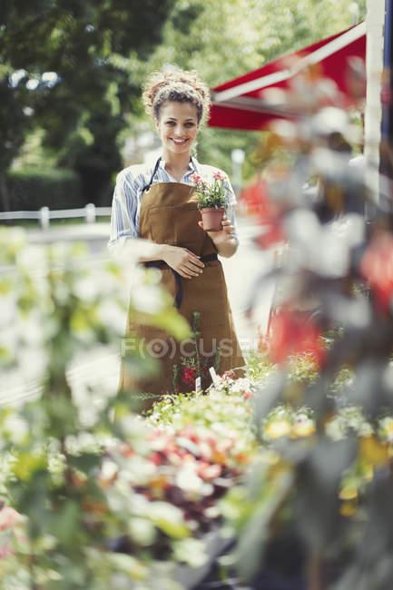 Portrait smiling female florist holding potted plant at flower shop storefront — Stock Photo
